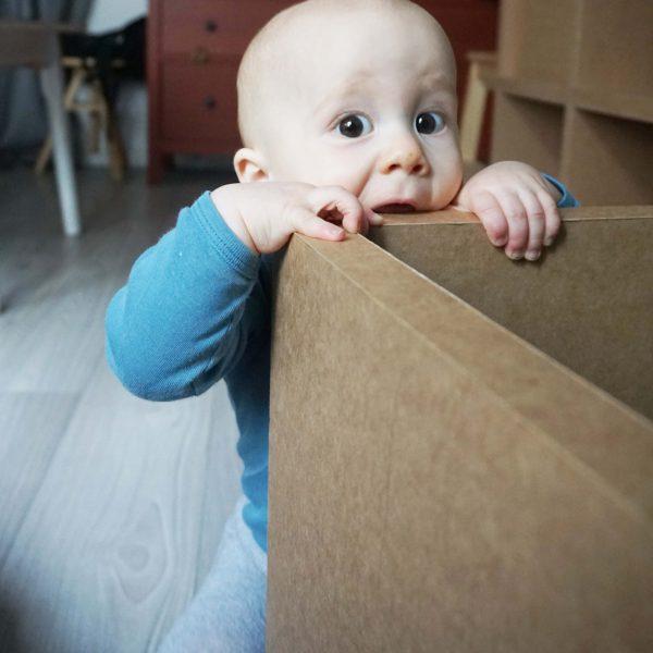 Baby klettert auf Papphocker